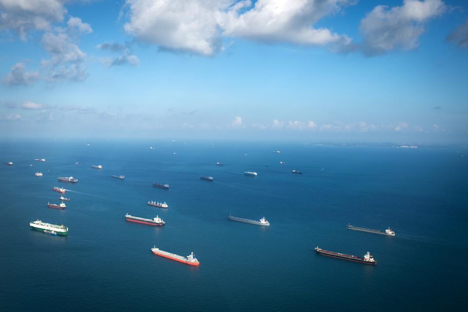 Singapore, Singapore: Transportation and Container ships wait on the ocean in front of the port of Singapore.