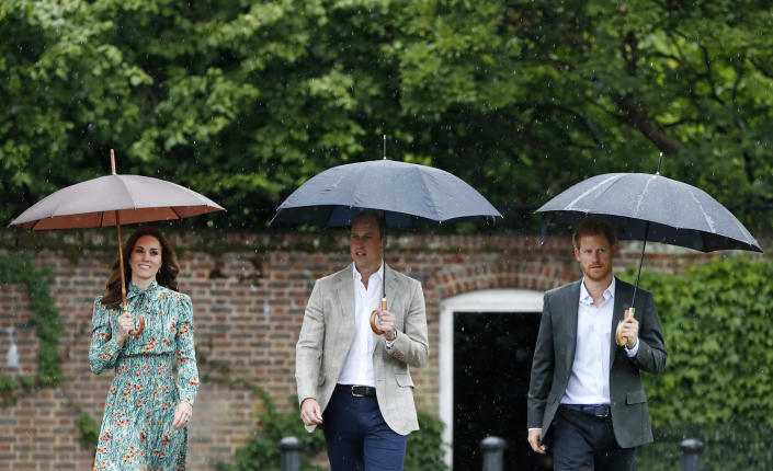 TOPSHOT - Britain's Prince William, Duke of Cambridge (C), his wife Britain's Catherine, Duchess of Cambridge (L) and his brother Britain's Prince Harry, shelter from the rain beneath umbrellas as they arrive to attend an event at the memorial gardens in Kensington Palace, west London on August 30, 2017. Princes William and Harry prepared to pay tribute to their late mother Princess Diana on Wednesday for the 20th anniversary of her death as wellwishers left candles and flowers outside the gates of her former London residence. / AFP PHOTO / POOL / Kirsty Wigglesworth        (Photo credit should read KIRSTY WIGGLESWORTH/AFP via Getty Images)