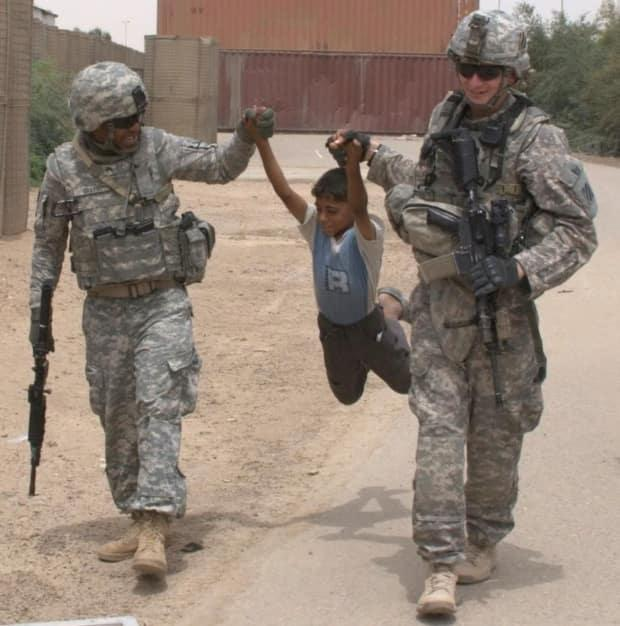 All three of the plaintiffs are U.S. military veterans. Here, Johnny Grays, left, is shown during an army deployment to Iraq in 2009 with a colleague and child.