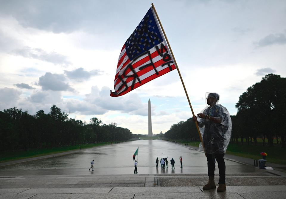 """A demonstrator waves an American flag with the words """"Not Free"""" painted on it in front of the Washington Monument during a Juneteenth march and rally in Washington, DC, on June 19, 2020."""