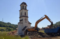 An orthodox church is demolished in Konjevic Polje, the village next to Srebrenica in Bosnia, Saturday, June 5, 2021. Bosnian authorities have demolished a Serbian Orthodox church illegally built on the land owned by a Bosniak woman after a 20-year-long legal battle that reached the European Court of Human Rights. Workers and construction machinery arrived at Fata Orlovic's yard in the village of Konjevic Polje early Saturday. (AP Photo/Sladjan Vasic)