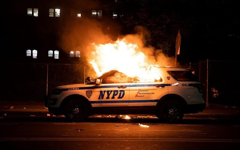 A NYPD police car is set on fire - Jennah Moon/Reuters