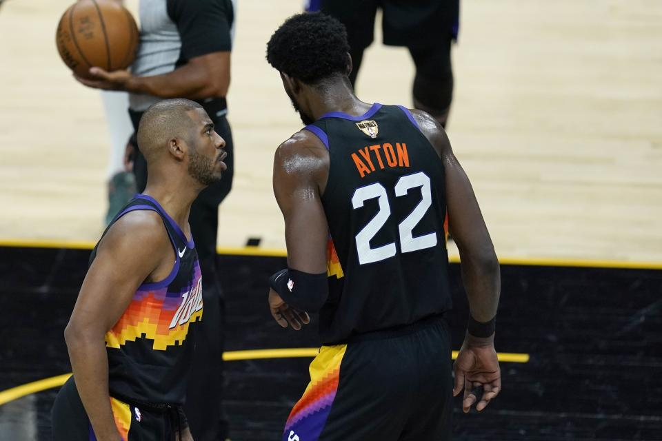 Phoenix Suns guard Chris Paul, left, talks with Suns center Deandre Ayton (22) during the first half of Game 1 of basketball's NBA Finals against the Milwaukee Bucks, Tuesday, July 6, 2021, in Phoenix. (AP Photo/Ross D. Franklin)