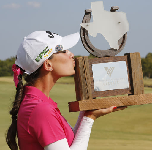 Cheyenne Knight, from Aledo, Texas, kisses the trophy after winning the LPGA Volunteers of America golf tournament Sunday, Oct. 6, 2019, at Old American Golf Club in The Colony, Texas. (AP Photo/David Kent)
