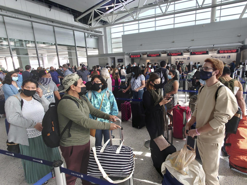 Airline passengers wait to check-in at George Bush Intercontinental Airport Sunday, May 16, 2021, in Houston. Airline travel is increasing as more Americans are getting the COVID-19 vaccination. (AP Photo/David J. Phillip)
