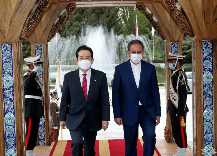 In this photo released by the official website of the office of the Iranian Senior Vice- President, Senior Vice-President Eshaq Jahangiri, right, and South Korea's Prime Minister Chung Sye-kyun walk during a welcoming ceremony for Sye-kyun in Tehran, Iran, Sunday, April 11, 2021. (Office of the Iranian Vice President via AP)