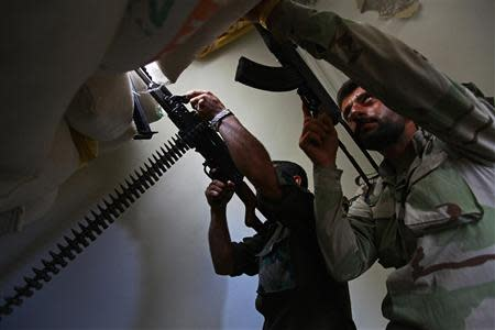 Free Syrian Army fighters aim their weapons as they take defensive positions in Aleppo