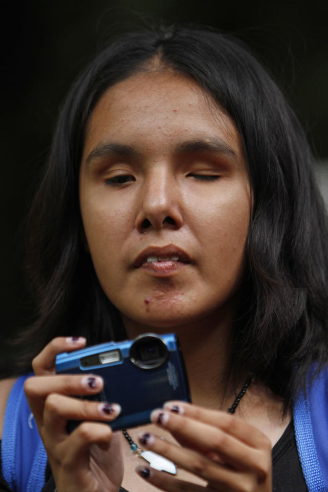 In this photo taken Sept. 7, 2011, Nancy Sarahi feels her camera as she prepares to take a photograph at a park in Mexico City. Sarahi is one of 30 visually impaired or blind people learning photography with the help of the Mexico City foundation Ojos Que Sienten, or Eyes That Feel. (AP Photo/Marco Ugarte)