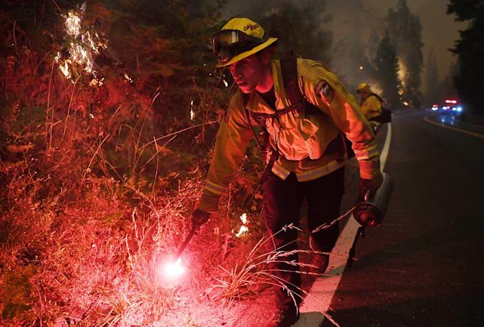 Cal Fire's Ricardo Gomez sets fire to dry grass as part of a back-burning effort along Highway 168 at the edge of Shaver Lake in a bid to help slow the spread of the Creek Fire on Sunday, Sept. 6, 2020.