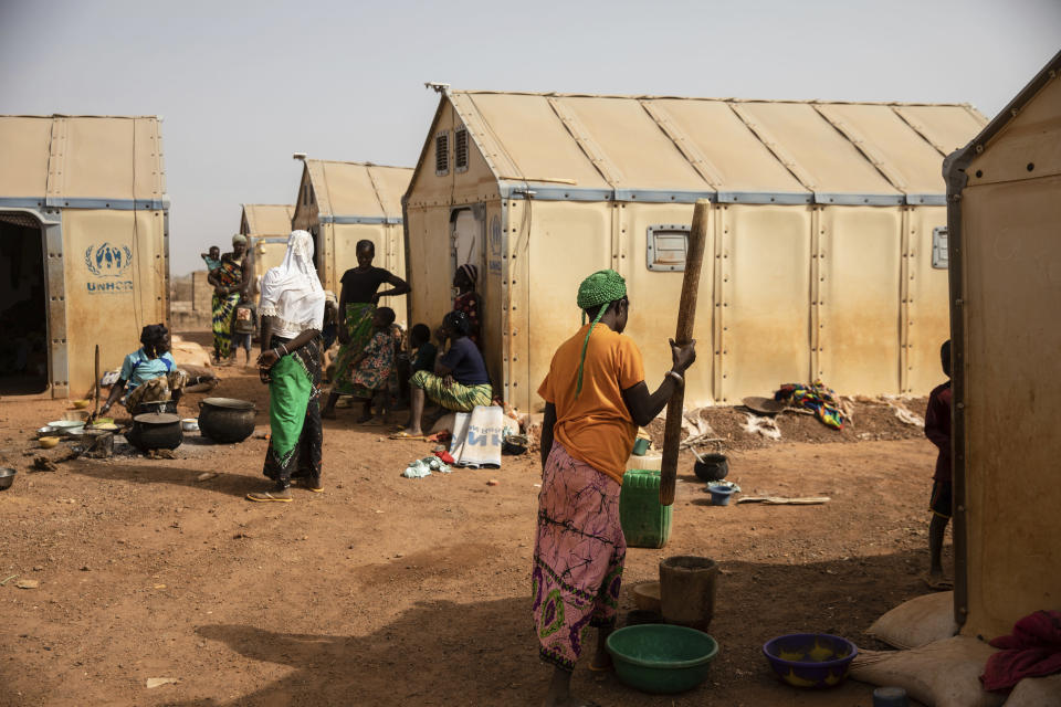 Displaced women prepare food Monday Feb. 8, 2021 in the Kaya camp, 100 kms North of Ouagadougou, Burkina Faso. A report by humanitarian groups says sexual assault cases in one region increased five-fold during a three-month period in 2020. Aid groups say jihadists are not the only perpetrators and that there has been a sharp increase in domestic violence and exploitation of displaced women by host communities. (AP Photo/Sophie Garcia)