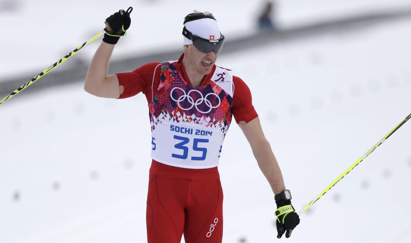 Switzerland's Dario Cologna crosses the finish line to win the gold during the men's 15K classical-style cross-country race at the 2014 Winter Olympics, Friday, Feb. 14, 2014, in Krasnaya Polyana, Russia. (AP Photo/Matthias Schrader)