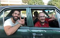 Best friends Bader al-Hajjami (R) and Ahmad Moussa pose during a car ride in Syria's capital Damascus; Bader is paralysed from the waist down, while Ahmad cannot hear or speak