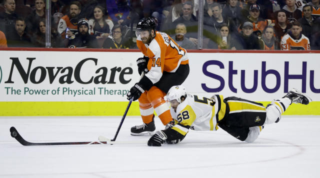 Pittsburgh Penguins' Kris Letang (58) dives to keep the puck away from Philadelphia Flyers' Sean Couturier (14) during the second period of an NHL hockey game, Monday, Feb. 11, 2019, in Philadelphia. (AP Photo/Matt Slocum)