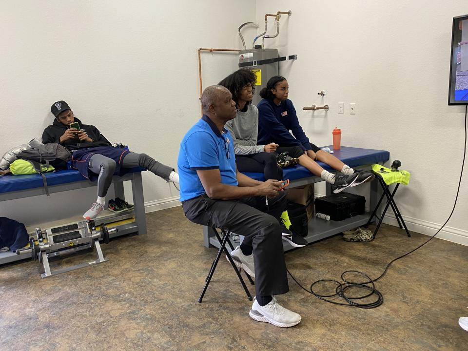 Randall Cunningham, in blue, and Vashti Cunningham, in gray, watch video of practice at the Cunningham compound in Las Vegas. (Yahoo Sports)