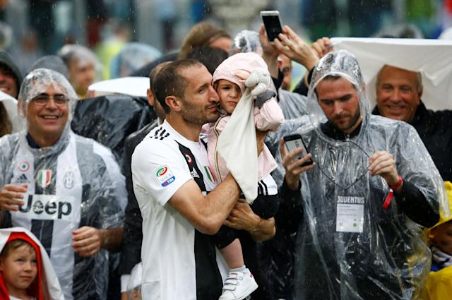 Soccer Football - Serie A - Juventus vs Hellas Verona - Allianz Stadium, Turin, Italy - May 19, 2018 Juventus' Giorgio Chiellini celebrates with child on the pitch at the end of the match REUTERS/Stefano Rellandini