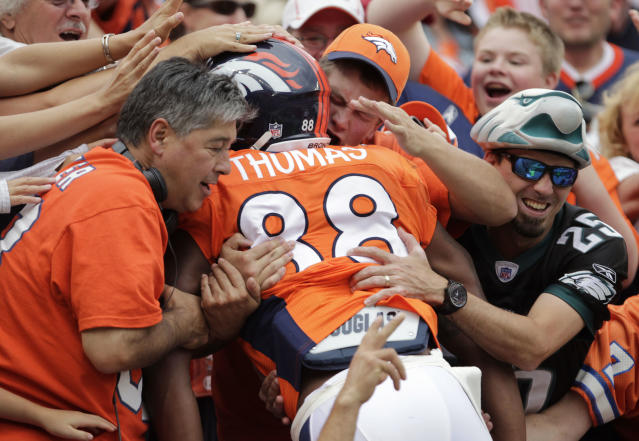 Denver Broncos wide receiver Demaryius Thomas (88) is mobbed by fans as he jumps into the stands after scoring a touchdown against the Philadelphia Eagles in the third quarter of an NFL football game, Sunday, Sept. 29, 2013, in Denver. (AP Photo/Joe Mahoney)