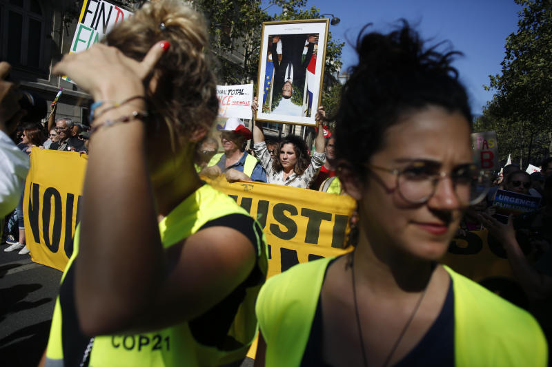A woman holds an upside down portrait of French President Emmanuel Macron during a climate demonstration, in Paris, Saturday, Sept. 21, 2019. Scuffles broke out in Paris between some violent activists and police which responded with tear gas at a march for climate gathering thousands of people in Paris. (AP Photo/Thibault Camus)