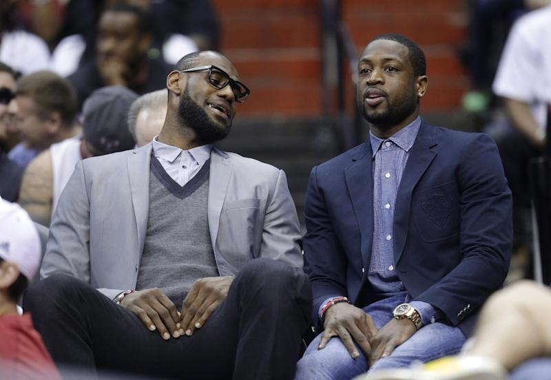 Miami Heat's LeBron James, left, and Dwyane Wade sit on the bench during the first half of an NBA basketball game against the Washington Wizards on Wednesday, April 10, 2013, in Washington. (AP Photo/Evan Vucci)