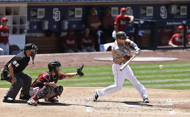 San Diego Padres' Chris Denorfia slams a run producing single to right field against the Arizona Diamondbacks during the third inning of a baseball game Sunday, May 4, 2014, in San Diego. (AP Photo/Lenny Ignelzi)