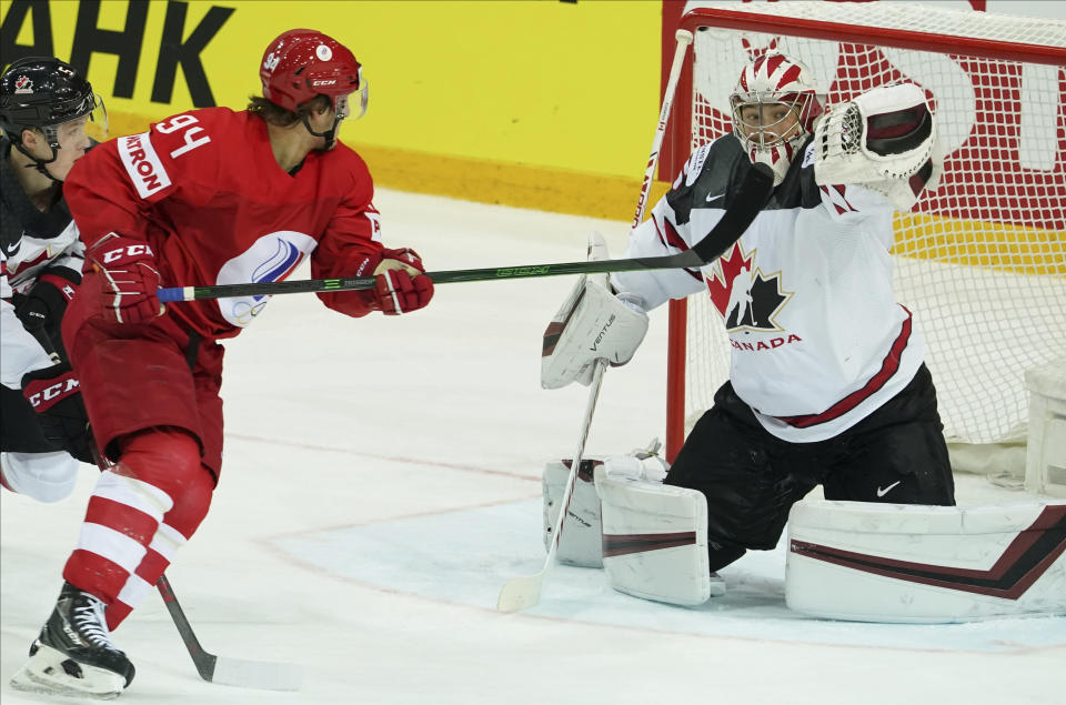 Alexander Barabanov of Russia, left, fight for a puck with Darcy Kuemper of Canada during the Ice Hockey World Championship quarterfinal match between Russia and Canada at the Olympic Sports Center in Riga, Latvia, Thursday, June 3, 2021. (AP Photo/Roman Koksarov)