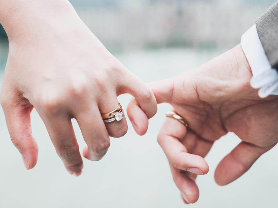 A newly wed couple doing a pinky promise (Getty Images/iStockphoto)