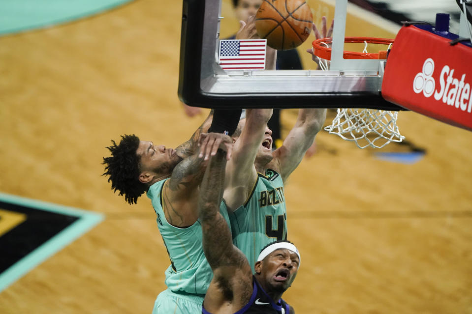 Charlotte Hornets center Cody Zeller shoots over Phoenix Suns forward Torrey Craig as forward Miles Bridges, left, looks on during the first half of an NBA basketball game on Sunday, March 28, 2021, in Charlotte, N.C. (AP Photo/Chris Carlson)