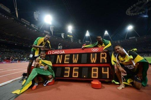 From L: Jamaica's Usain Bolt, Yohan Blake, Nesta Carter, Michael Frater pose by the record board after setting a new world record in the men's 4X100m relay final at the athletics event of the London 2012 Olympic Games