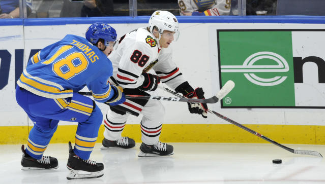 St. Louis Blues' Robert Thomas (18) and Chicago Blackhawks' Patrick Kane (88) reach for the puck during the second period of an NHL hockey game, Saturday, Oct. 27, 2018, in St. Louis. (AP Photo/Bill Boyce)