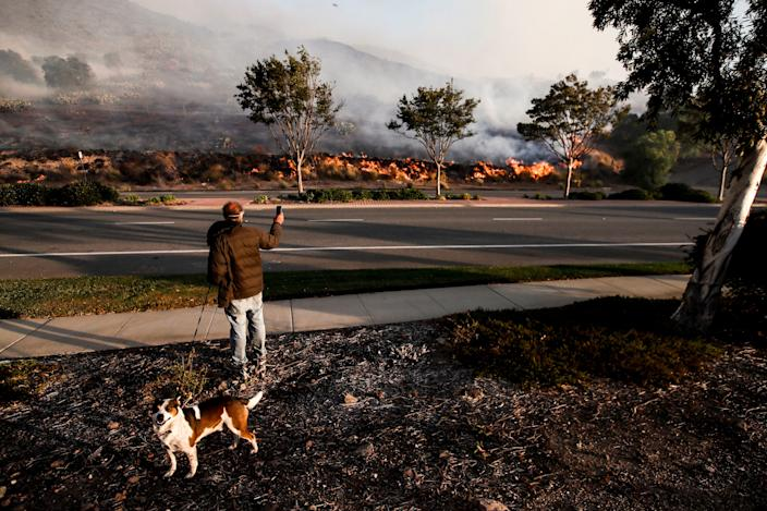 A resident watches from the side of the road the Easy Fire spreading in Simi Valley, North of Los Angeles, Calif., on Oct. 30, 2019. (Photo: Etienne Laurent/EPA-EFE/Shutterstock)