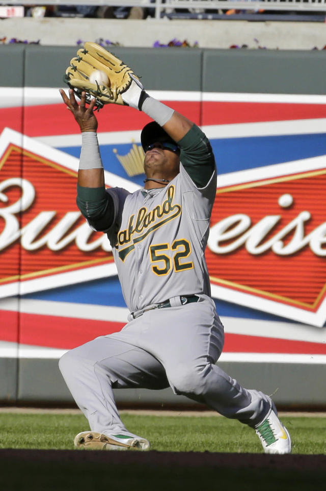 Oakland Athletics left fielder Yoenis Cespedes (52) catches a fly ball by Minnesota Twins catcher Kurt Suzuki during the sixth inning of a home opener baseball game in Minneapolis, Monday, April 7, 2014. (AP Photo/Ann Heisenfelt)
