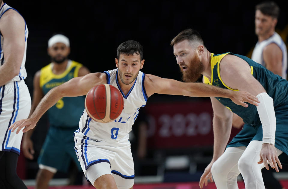 Italy's Marco Spissu (0) and Australia's Aron Baynes (12) chase a loose ball during a men's basketball preliminary round game at the 2020 Summer Olympics, Wednesday, July 28, 2021, in Saitama, Japan. (AP Photo/Eric Gay)