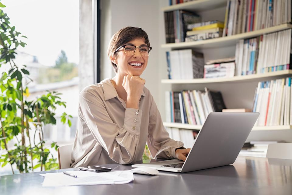 Successful young business woman sitting in creative office and looking at camera. Portrait of happy entrepreneur with hand on chin working on computer. Smiling businesswoman using laptop while working from home.