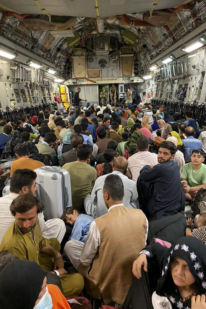 Afghan people sit inside a U S military aircraft to leave Afghanistan, at the military airport in Kabul on August 19, 2021.