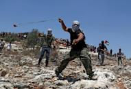 Palestinians in Beita hurl rocks by slingshot, while protesting against the Eviatar outpost