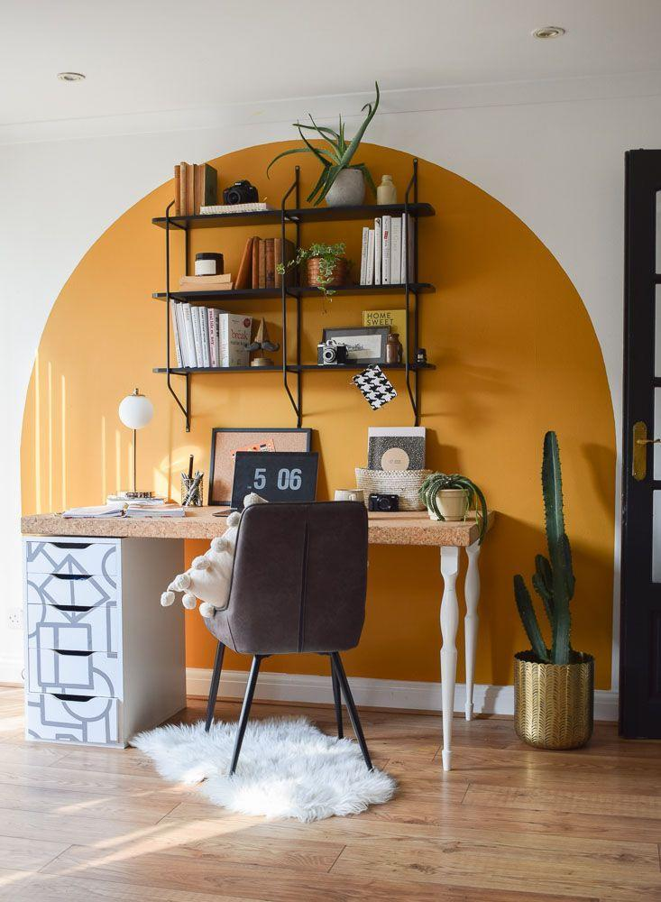 """<p>""""I needed a space in my home to work, as my husband also now works from home too. I created this office in my dining room, and painted a large sunny arch to zone it all. Yellow is my favourite colour and so working here in the day always lifts my mood. The shelves are from <a href=""""https://www.next.co.uk/shop/department-homeware/?gclid=Cj0KCQiA7NKBBhDBARIsAHbXCB52tbOQTbZoy8NCPnuw0M_YeIYJ_vhJpbKVo5K1jFH9qrOYF1mx1iAaAnBXEALw_wcB&gclsrc=aw.ds"""" rel=""""nofollow noopener"""" target=""""_blank"""" data-ylk=""""slk:Next Home"""" class=""""link rapid-noclick-resp"""">Next Home</a>, and the table is an old dining table that I repurposed into a desk.""""</p>"""
