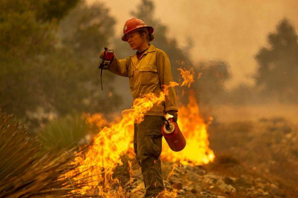 PHOTO: MONROVIA, CA - SEPTEMBER 10: Mormon Lake Hotshots firefighter Sara Sweeney uses a drip torch to set a backfire to protect mountain communities from the Bobcat Fire in the Angeles National Forest on September 10, 2020 north of Monrovia, California. (David Mcnew/Getty Images)