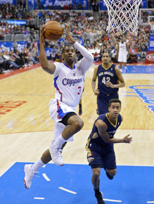 Los Angeles Clippers guard Chris Paul, left, goes up for a shot as New Orleans Pelicans guard Brian Roberts, lower right, defends while center Alexis Ajinca, of France, looks on during the first half of an NBA basketball game, Saturday, March 1, 2014, in Los Angeles. (AP Photo/Mark J. Terrill)
