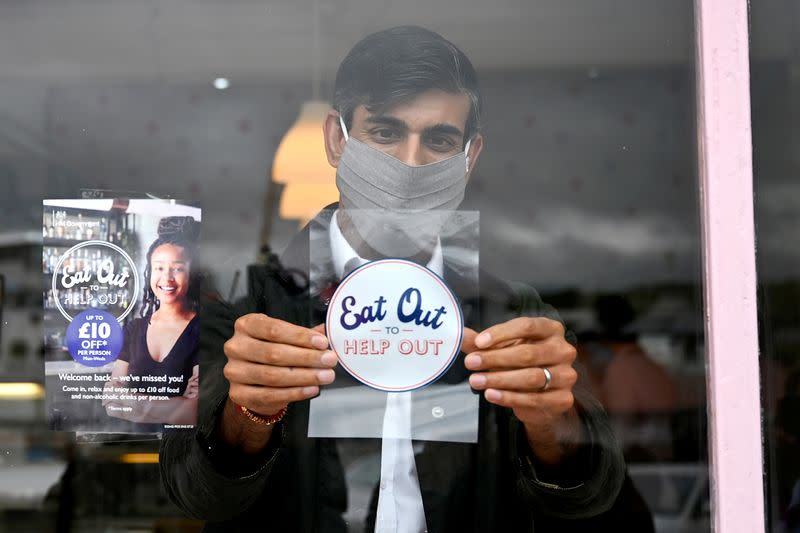 FILE PHOTO: Britain's Chancellor of the Exchequer Rishi Sunak, wearing a face mask, places a sticker as he meets with local business people during a visit to Rothesay, in the Isle of Bute, Scotland