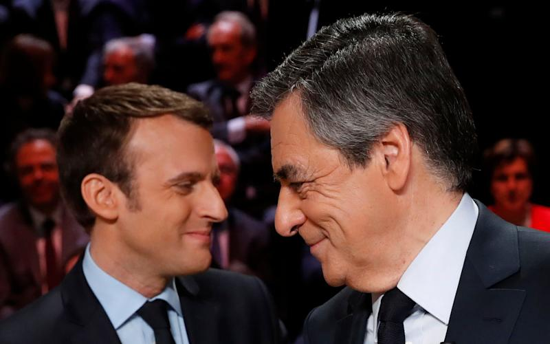 Emmanuel Macron, left, greets Francois Fillon ahead of the televised debate - Credit: AP