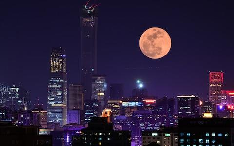 A super blood moon rises over buildings on January 31, 2018 in Beijing, China - Credit: VCG