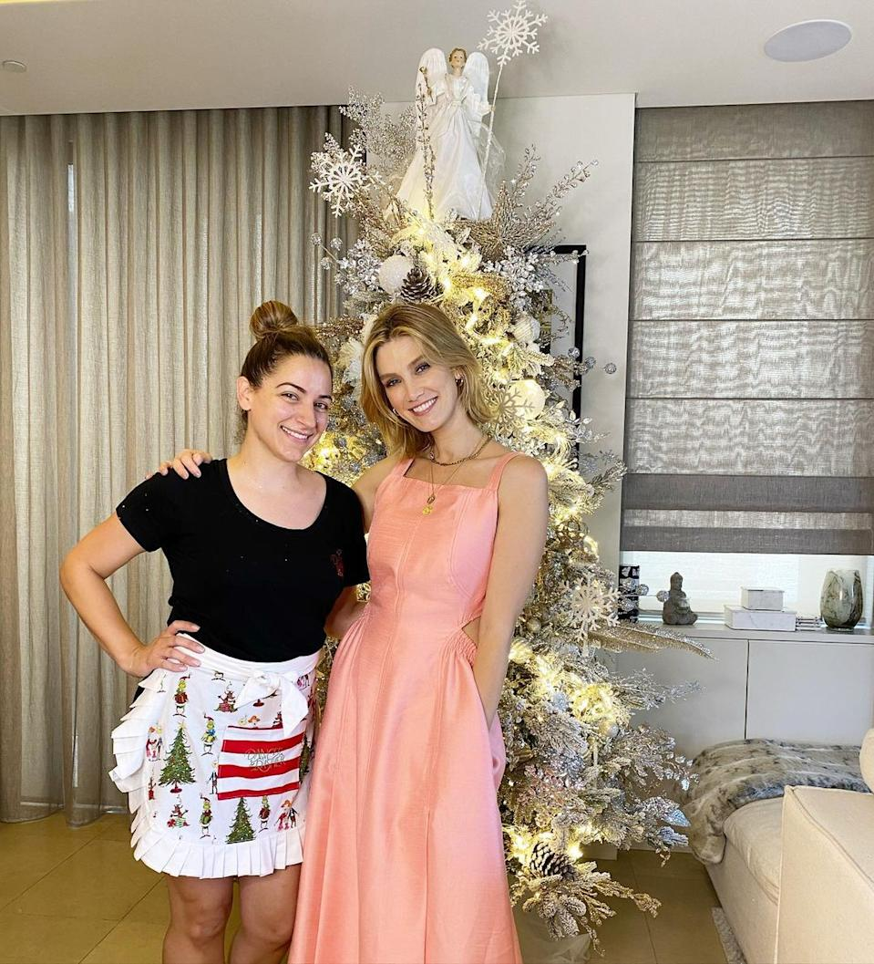 Delta Goodrem poses in front of her Christmas tree with a professional stylist