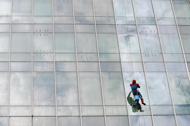 SURABAYA, INDONESIA - JULY 12: Indonesian 'Spider-Man' window cleaner, 37-year-old Teguh cleans the glass windows of the 18-storey Alana Hotel on July 12, 2013 in Surabaya, Indonesia. Teguh is a specialist glass window cleaner working on high-rise buildings wearing a Spider-Man uniform and working at an altitude of over 500 meters above ground level. He earns between Rp. 5 million and 15 million depending on the height of the building and the level of difficulty. (Photo by Robertus Pudyanto/Getty Images)