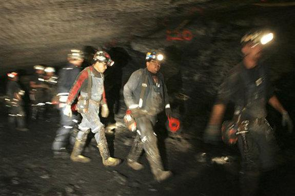 Rescuers work near the blocked tunnel in Utah's Crandall Canyon mine where six coal miners are trapped.