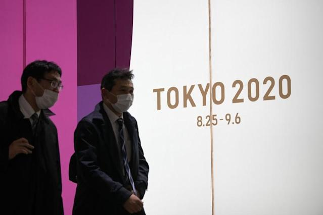 """Two people in Tokyo pass a sign promoting the now postponed Olympics. <span class=""""copyright"""">(Carl Court / Getty Images)</span>"""