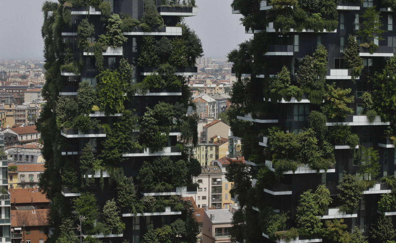 In this picture taken on Aug. 3, 2017 a partial view of the vertical forest residential towers at the Porta Nuova district, in Milan, Italy. If Italy's fashion capital has a predominant color, it is gray not only because of the blocks of uninterrupted neoclassical stone buildings for which the city is celebrated, but also due to the often-gray sky that traps in pollution. The city has ambitious plans to plant 3 million new trees by 2030_ a move that experts say could offer relief to the city's muggy and sometimes tropical weather. (AP Photo/Luca Bruno)