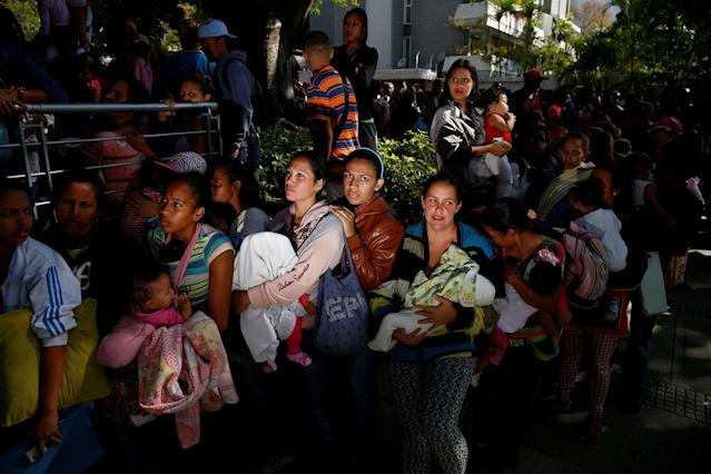 <p>MAR. 18, 2017 – Women carrying babies queue as they try to buy diapers outside a pharmacy in Caracas, Venezuela. Going into a fourth year of crippling recession, Venezuela's 30 million people found themselves skipping meals, suffering shortages of basic foods and medicines, jostling in lines for ever-scarcer subsidized goods, unable to keep up with dizzying inflation rates, and emigrating in ever larger numbers. (Photo: Carlos Garcia Rawlins/Reuters) </p>