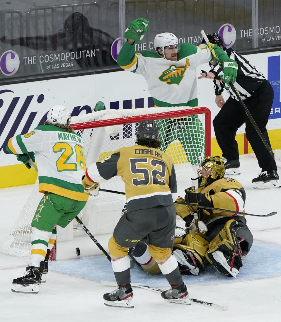 Minnesota Wild left wing Marcus Foligno, top right, celebrates after scoring against Vegas Golden Knights goaltender Marc-Andre Fleury (29) during the second period of an NHL hockey game Wednesday, March 3, 2021, in Las Vegas. (AP Photo/John Locher)