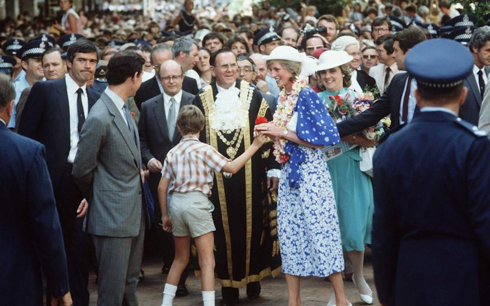 The Prince and Princess Of Wales on a walkabout in Brisbane, Australia, with the the Hon. Edward Adeane (right of Prince Charles in picture -balding with glasses) - Tim Graham/Getty Images