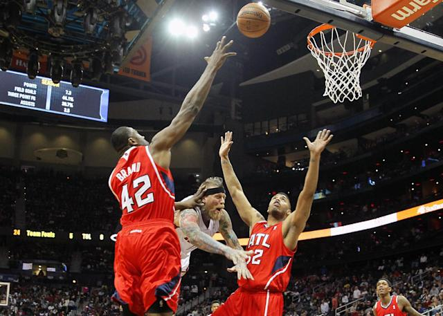 Miami Heat power forward Chris Andersen (11) shoots as he is defended by Atlanta Hawks power forward Elton Brand (42) and power forward Mike Scott (32) in the first period of an NBA basketball game in Atlanta, Monday, Jan. 20, 2014. (AP Photo/Todd Kirkland)