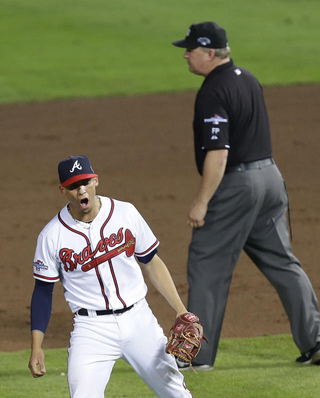 Atlanta Braves shortstop Andrelton Simmons, left, cheers after tagging out Los Angeles Dodgers' Dee Gordon who was trying to steal second base in the ninth inning of Game 2 of the National League division series on Friday, Oct. 4, 2013, in Atlanta. The Braves won 4-3. (AP Photo/Mike Zarrilli)